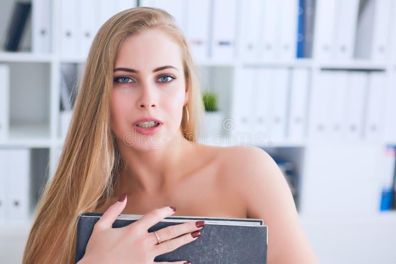 Schöner junger Sekretär versteckt ihre Nacktheit für einen Ordner auf einem Bürohintergrund Belästigungskonzept lizenzfreie stockfotos