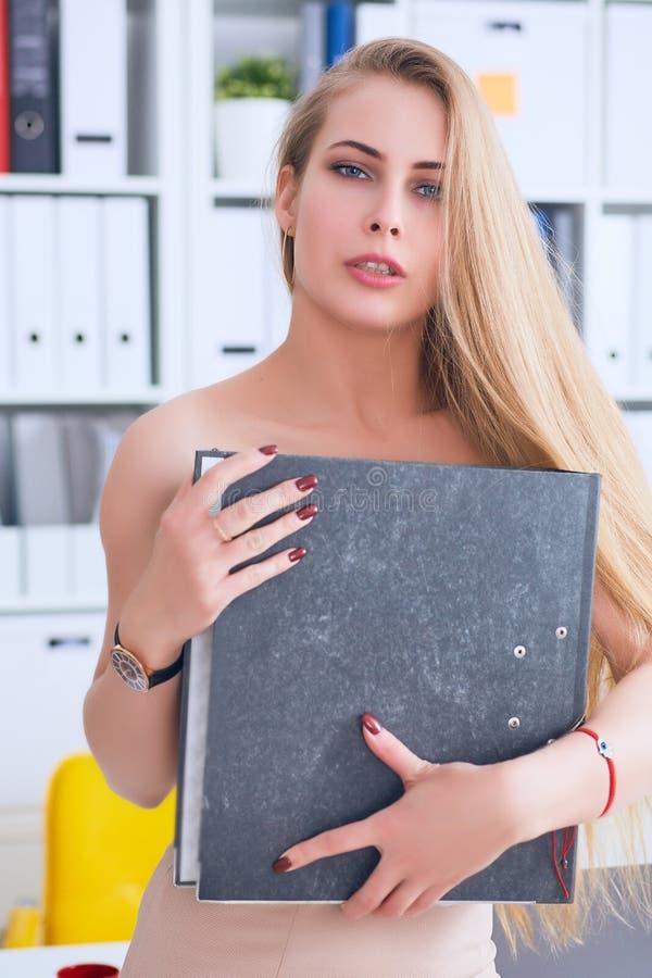Schöner junger Sekretär versteckt ihre Nacktheit für einen Ordner auf einem Bürohintergrund Belästigungskonzept stockbilder