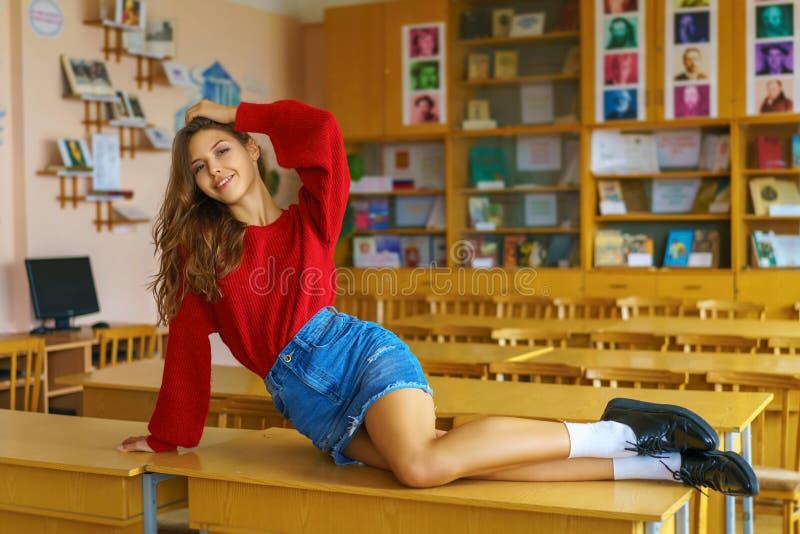Schöner junger sexy Student auf dem Tisch stockfotografie
