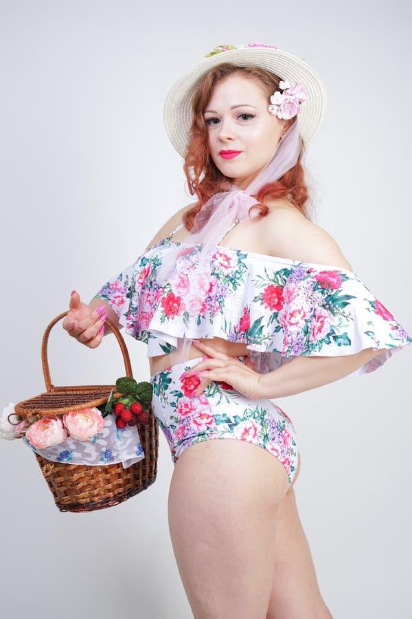 Schöner junger Stift herauf kaukasisches Mädchen im romantischen modernen Strohhut, im Weinlesebadeanzug mit Blumen und in Retro- lizenzfreies stockbild