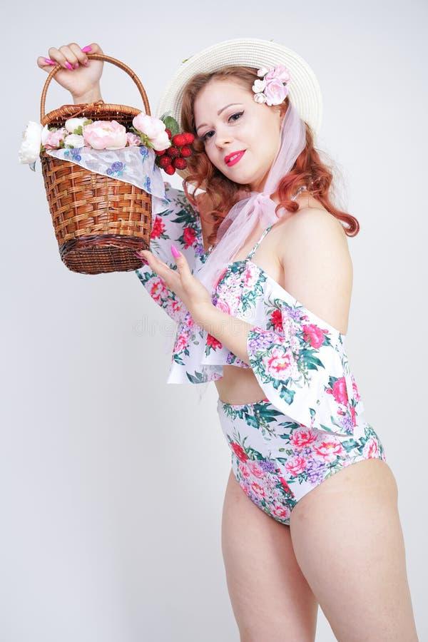 Schöner junger Stift herauf kaukasisches Mädchen im romantischen modernen Strohhut, im Weinlesebadeanzug mit Blumen und in Retro- lizenzfreies stockfoto
