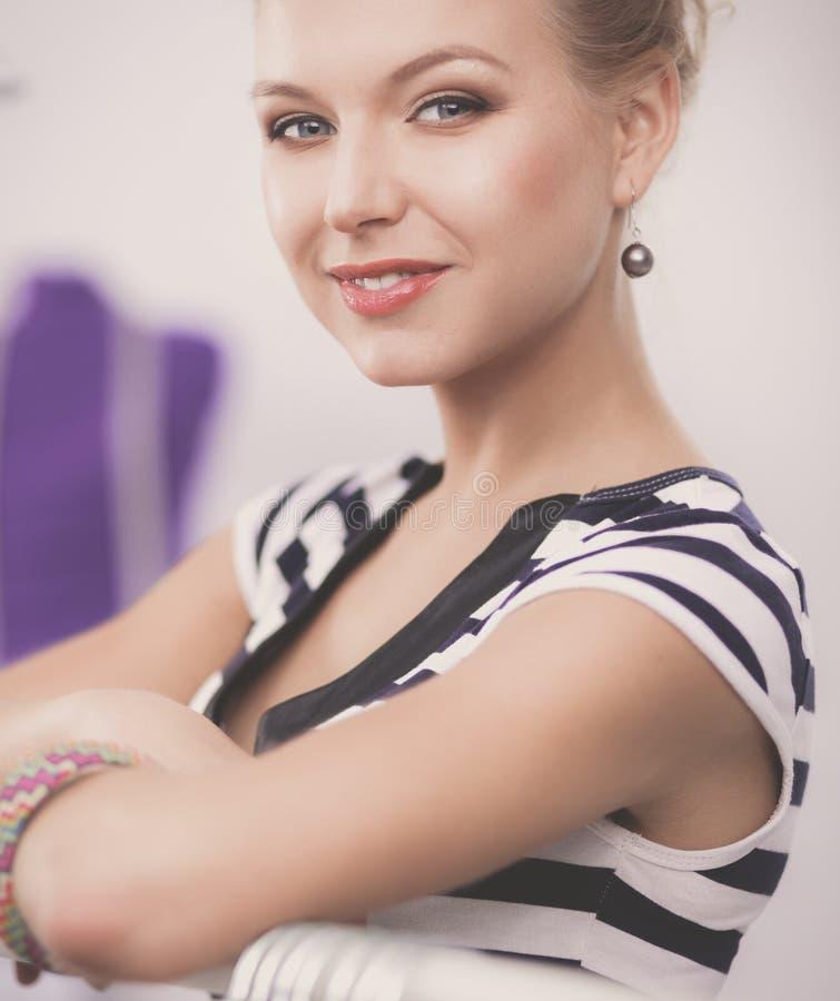 Schöner junger Stilist nahe Gestell mit Aufhängern im Büro stockfotografie