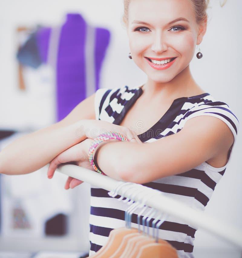Schöner junger Stilist nahe Gestell mit Aufhängern im Büro lizenzfreie stockbilder