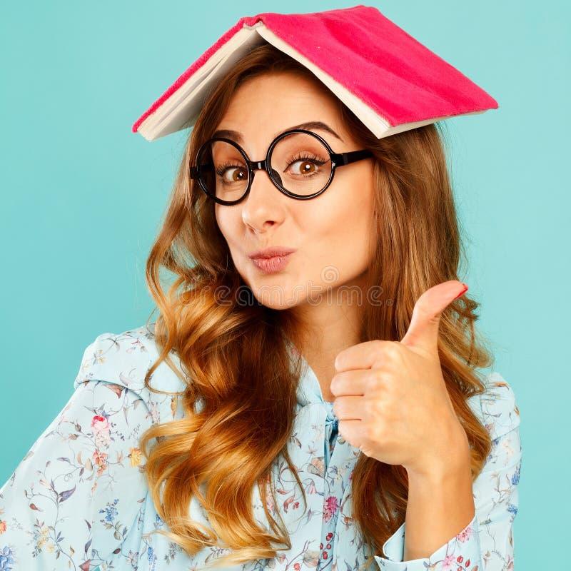 Schöner junger Student, der Buch auf ihrem Kopf hält und gla trägt stockbild