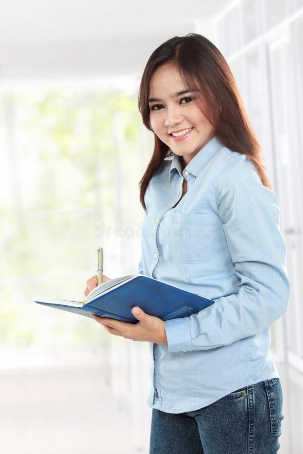 Schöner junger Student, der Buch und das Schreiben hält lizenzfreies stockfoto