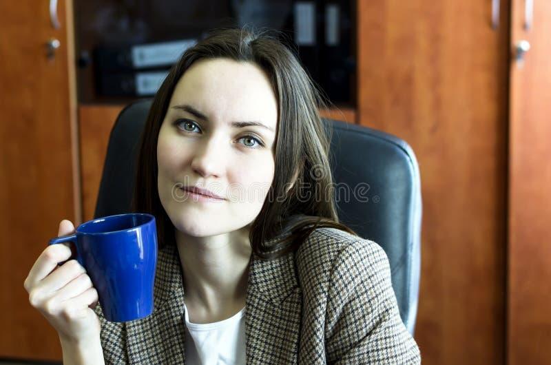 Schöner junger trinkender Kaffee der Geschäftsfrau im Büro lizenzfreies stockfoto
