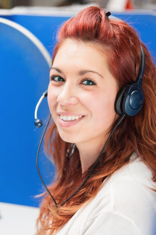 Schöner junger weiblicher Call-Center-Betreiber mit Kopfhörer im Büro stockfotografie