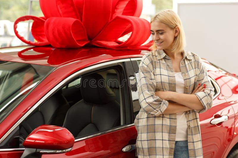 Schöner Kaufenneuwagen der jungen Frau an der Verkaufsstelle lizenzfreies stockfoto