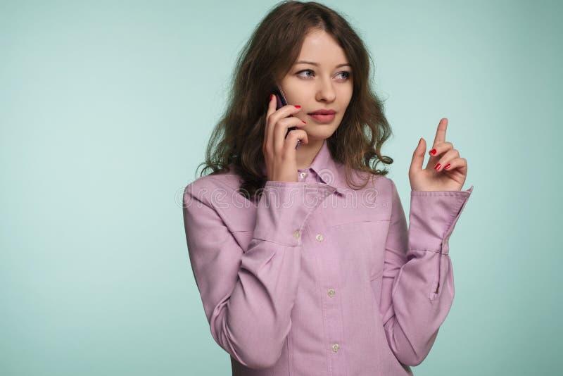 Schöner Kaukasier überraschtes junges Mädchen, das an ihrem Handy zeigt herauf Hintergrund spricht stockbild