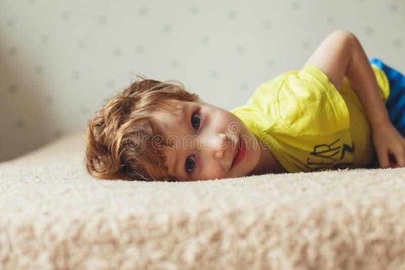 Schöner kleiner Junge, der auf Bett und dem Schauen liegt Gelocktes nettes Kleinkind stockbilder