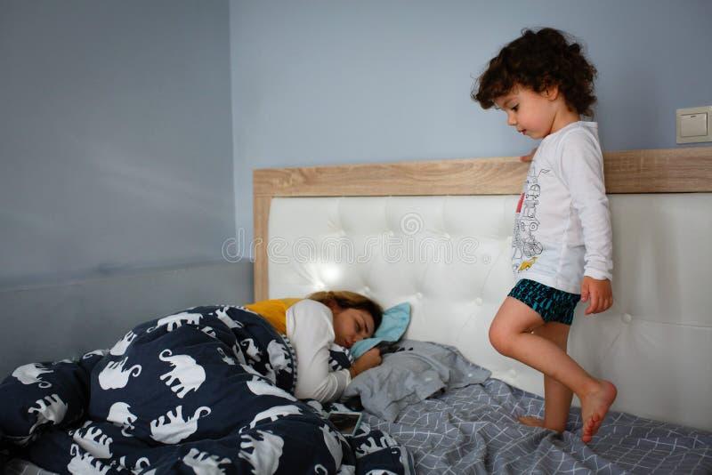 Schöner kleiner Junge, der auf dem Bett im Schlafzimmer nahe bei schlafender Mutter spielt stockfoto
