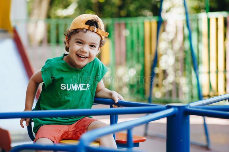 Schöner kleiner Junge, der sich auf einer Sommerschwinge mit Platz für Text dreht lizenzfreies stockbild