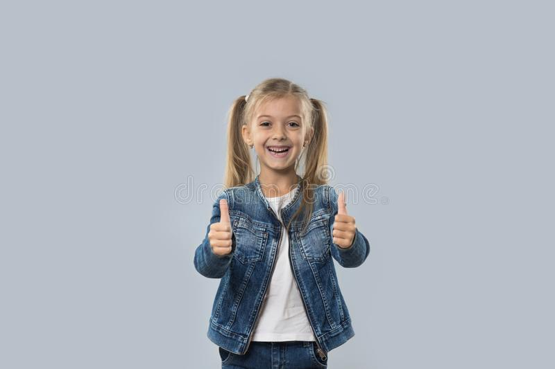 Schöner kleines Mädchen-aufgeregter Griff-Daumen herauf den glücklichen lächelnden Abnutzungs-Jeans-Mantel lokalisiert lizenzfreies stockbild