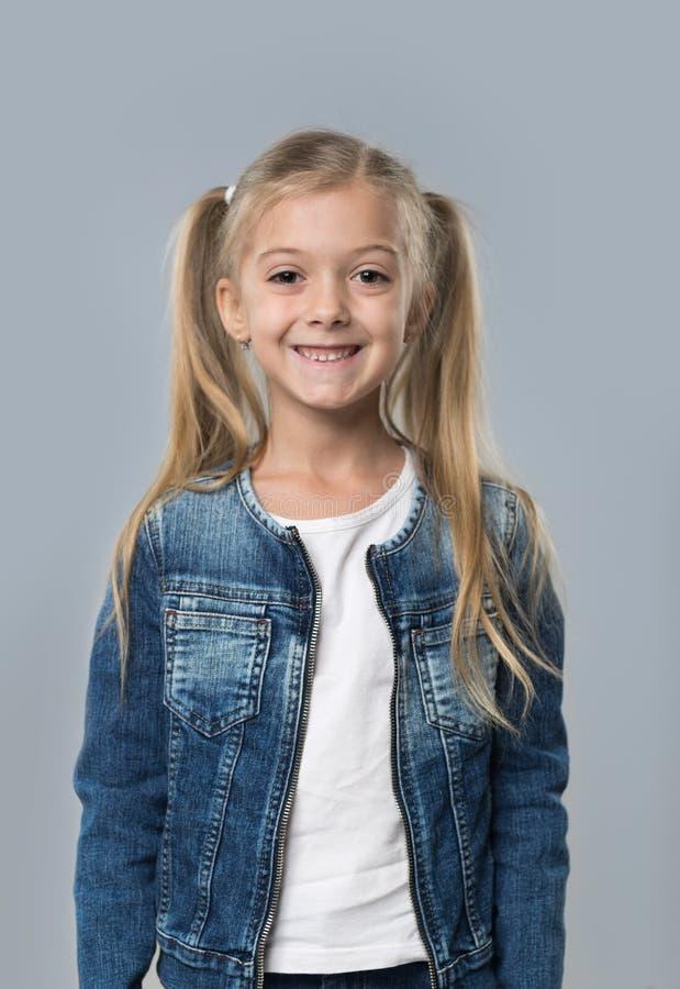 Schöner kleines Mädchen-glücklicher lächelnder Abnutzungs-Jeans-Mantel lokalisiert stockbilder