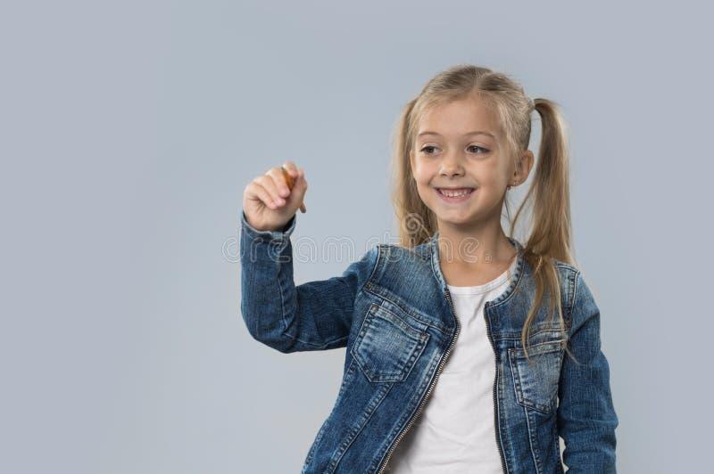 Schöner kleines Mädchen-Griff-Bleistift, der den glücklichen lächelnden Abnutzungs-Jeans-Mantel lokalisiert schreibt stockfoto