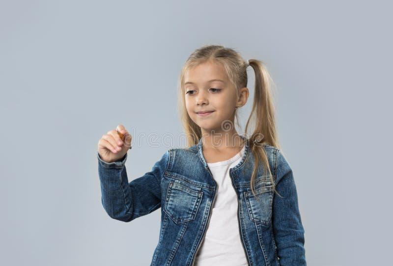 Schöner kleines Mädchen-Griff-Bleistift, der den glücklichen lächelnden Abnutzungs-Jeans-Mantel lokalisiert schreibt lizenzfreie stockfotografie