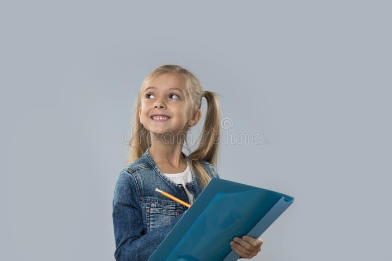 Schöner kleines Mädchen-Griff-Bleistift, der glücklichen lächelnden Blick schreibt, um den Raum zu kopieren lokalisiert lizenzfreie stockfotografie