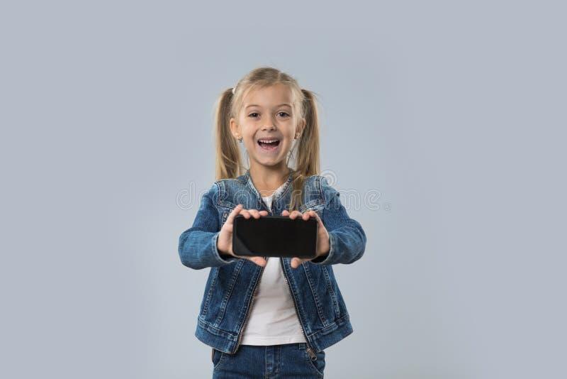 Schöner kleines Mädchen-Griff-Zellintelligenter Telefon-leerer Schirm-glücklicher lächelnder Abnutzungs-Jeans-Mantel lokalisiert lizenzfreie stockfotos