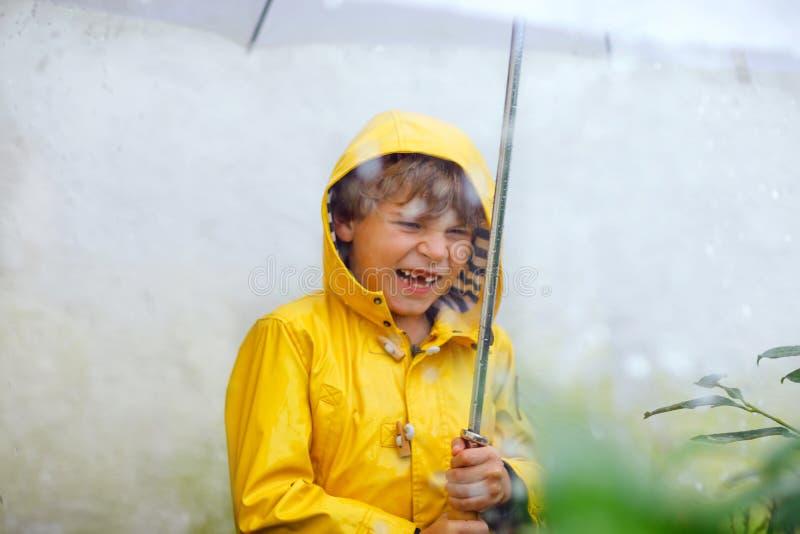 Schöner Kleinkindjunge auf Schulweg gehend während des Schneeregens, des starken Regens und des Schnees mit einem Regenschirm am  lizenzfreies stockbild