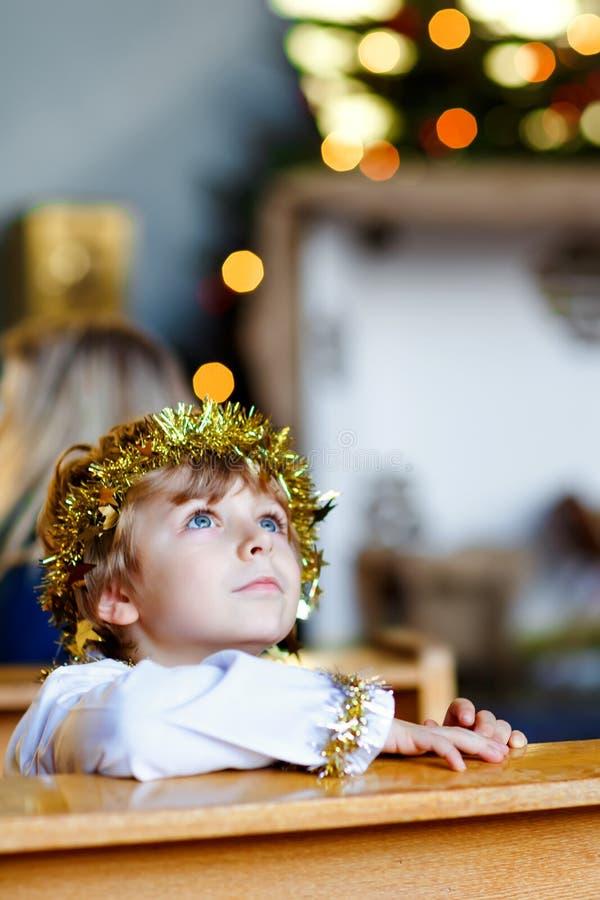 Schöner Kleinkindjunge, der einen Engel in der Weihnachtsgeschichte in einer Kirche spielt Glückliches entzückendes blondes Kind  stockfotografie