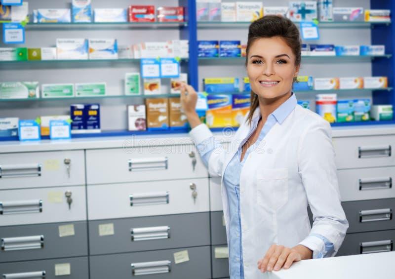 Schöner lächelnder Apotheker der jungen Frau, der seins Arbeit in der Apotheke tut stockbild