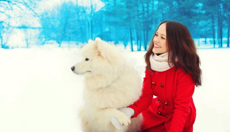 Schöner lächelnder Eigentümer der jungen Frau mit weißem Samoyedhund auf Schnee im Winter lizenzfreies stockbild