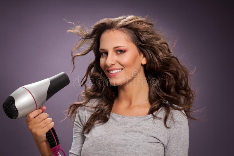Schöner lächelnder Frauenschlag, der ihr Haar trocknet stockbild