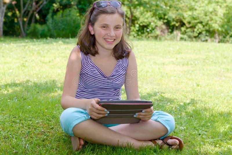 Schöner lächelnder Jugendlicher mit Tabletten-PC, draußen stockfotografie