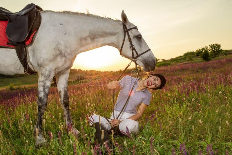 Schöner lächelnder Mädchenjockeystand nahe bei ihrem Schimmel, der spezielle Uniform auf einem Himmel und grünen einem Feldhinter lizenzfreie stockfotos