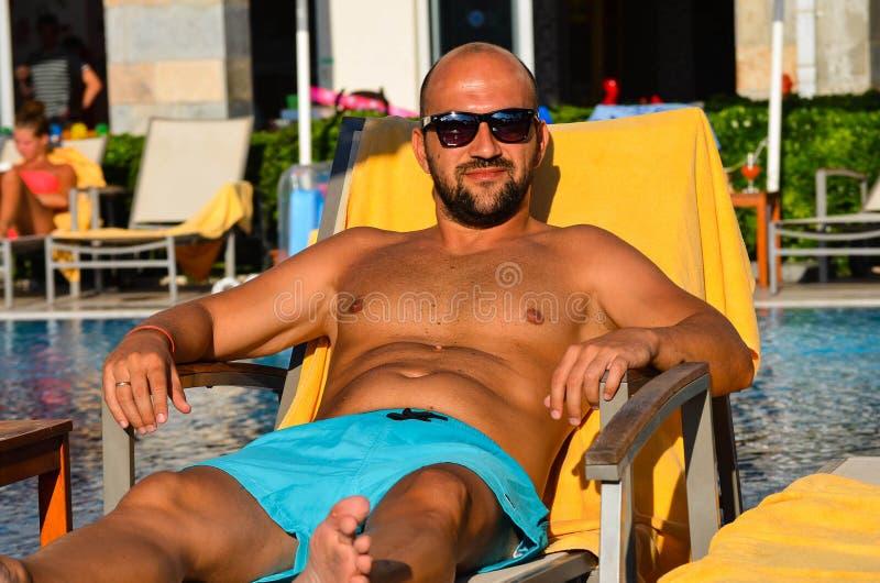 Schöner lächelnder Mann mit der Sonnenbrille und Ehering, die eine gute Zeit sich entspannen und lazing am Pool und haben stockbilder
