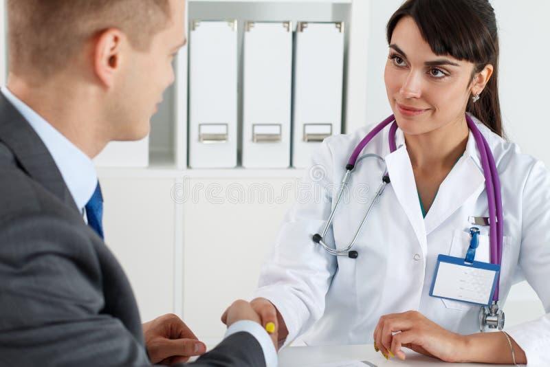 Schöner lächelnder weiblicher Medizindoktor, der Hände mit Mann rüttelt lizenzfreie stockfotos