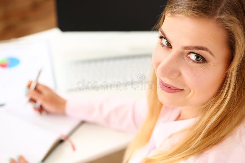 Schöner lächelnder weiblicher Sekretär, der am Büroarbeitsplatz sitzt stockfotografie
