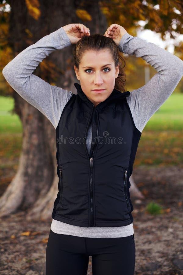 Schöner Läufer der jungen Frau, der im Park steht lizenzfreie stockfotografie