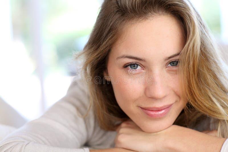 Schöner lehnender Kopf der jungen Frau auf ihren Händen stockfoto