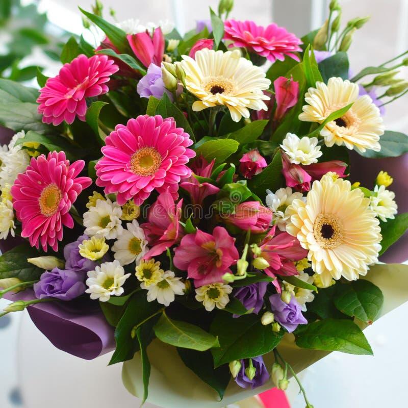 Schöner leicht Blumenstrauß auf weißer Tabelle an einem Fenster stockbilder