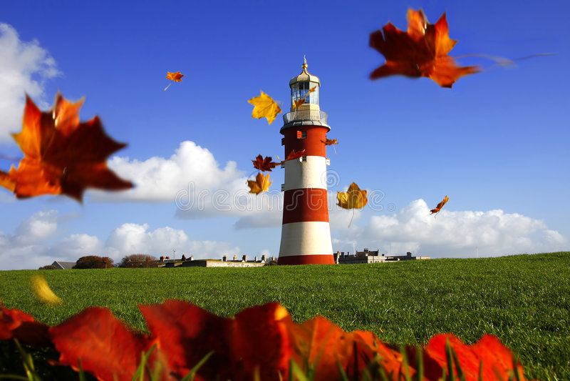 schöner Leuchtturm mit Flugwesenherbstblättern stockfotografie