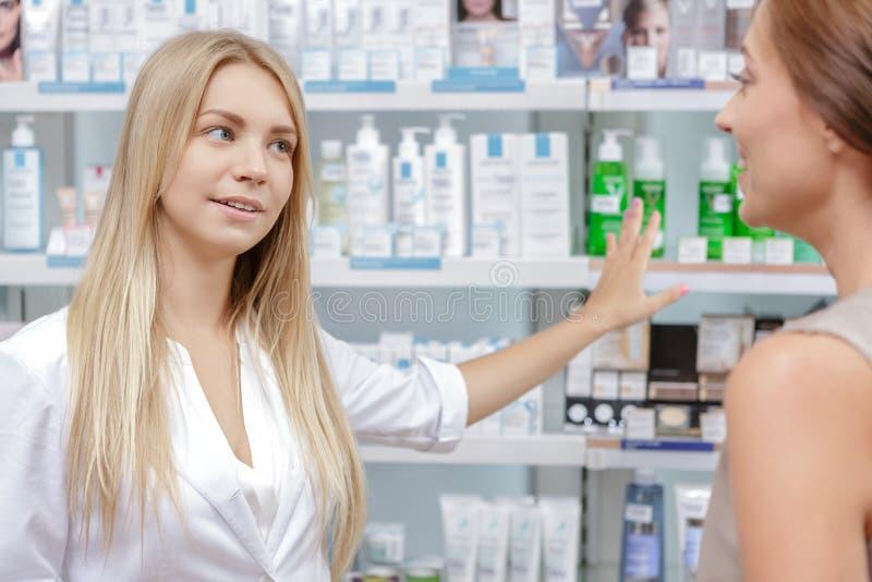 Schöner Mädchenapotheker, der einem Kunden hilft lizenzfreie stockfotografie