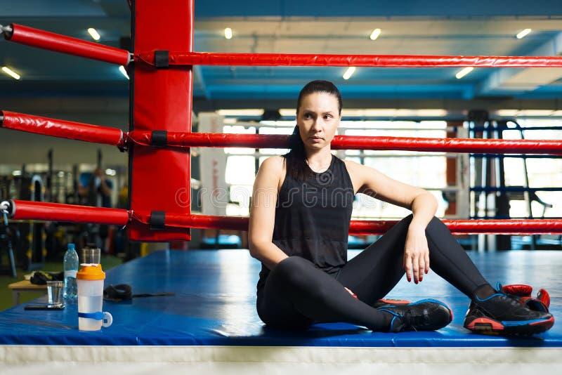 Schöner Mädchenathlet sitzt im Boxring in der Turnhalle es gibt eine Flasche Wasser auf dem Boden und den Handschuhen stockfotos