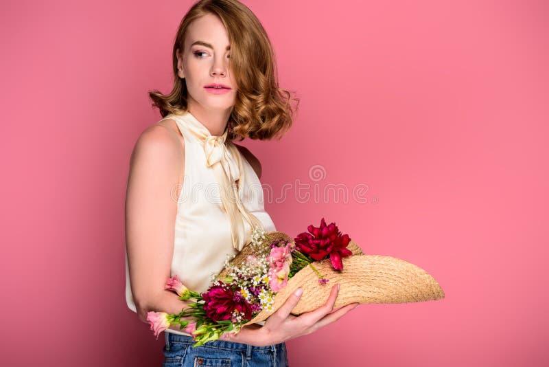 schöner Mädchenholdinghut mit Blumen und weg schauen stockfoto