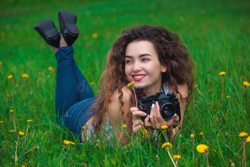 Schöner Mädchenphotograph mit dem gelockten Haar hält eine Kamera und auf dem Gras mit blühendem Löwenzahn im Frühjahr liegen dra lizenzfreie stockfotografie