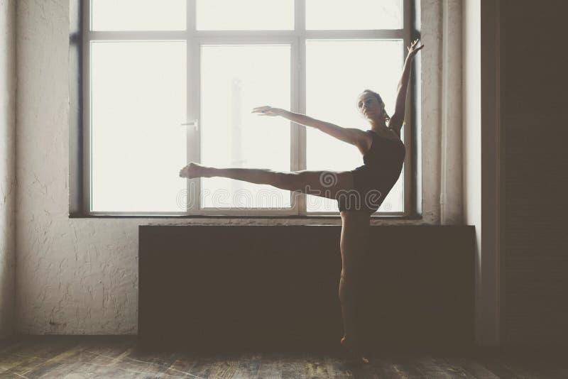 Schöner Mädchentänzer in der schwarzen Kleidung, in der schönen Haltung, hob gerades Bein über ihrem Kopf, Fuete gegen Fensterhin stockfotografie