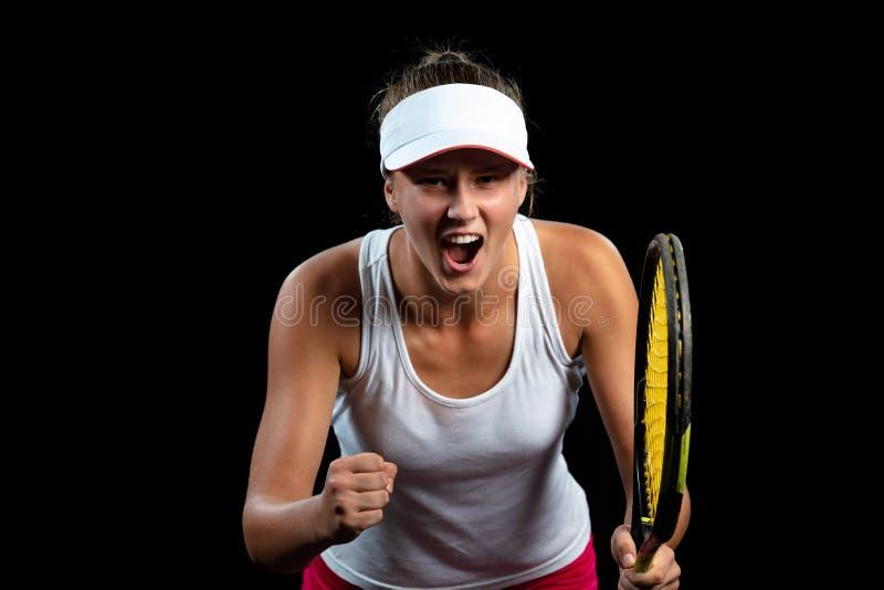 Schöner Mädchentennisspieler mit einem Schläger auf dunklem Hintergrund mit Lichtern fehlerlosen Sieg feiernd lizenzfreie stockfotografie