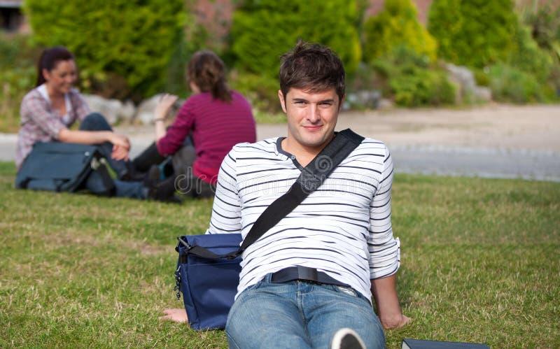 Schöner männlicher Kursteilnehmer, der mit seiner Schultasche liegt lizenzfreie stockfotos