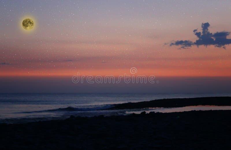 Schöner magischer rosa und blauer nächtlicher Himmel mit Wolken und Vollmond und Sterne nähern sich Meer lizenzfreie stockfotografie