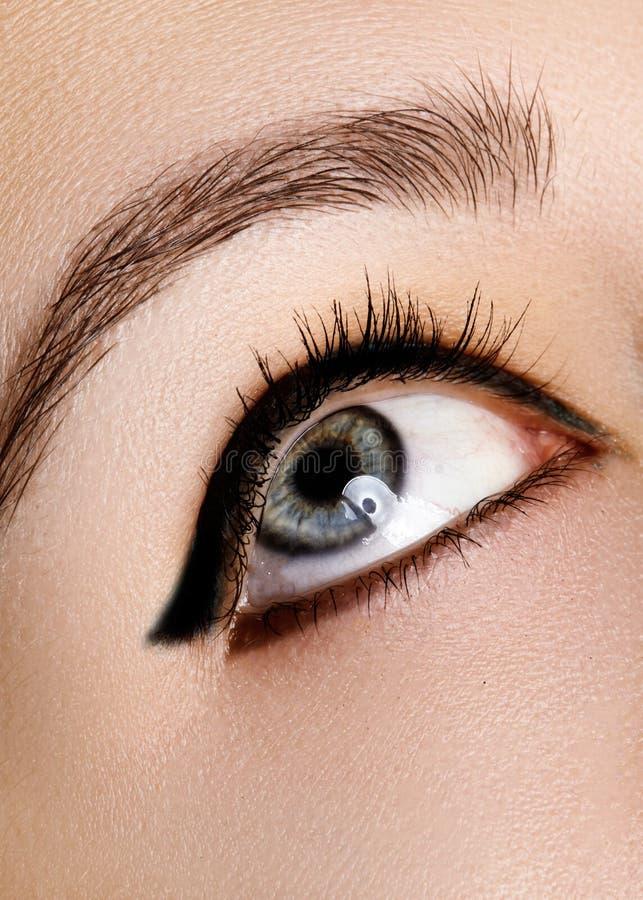 Schöner Makroschuß des weiblichen Auges mit Make-up Perfekte Form von Augenbrauen, blauer Eyeliner Kosmetik und Verfassung stockfotografie