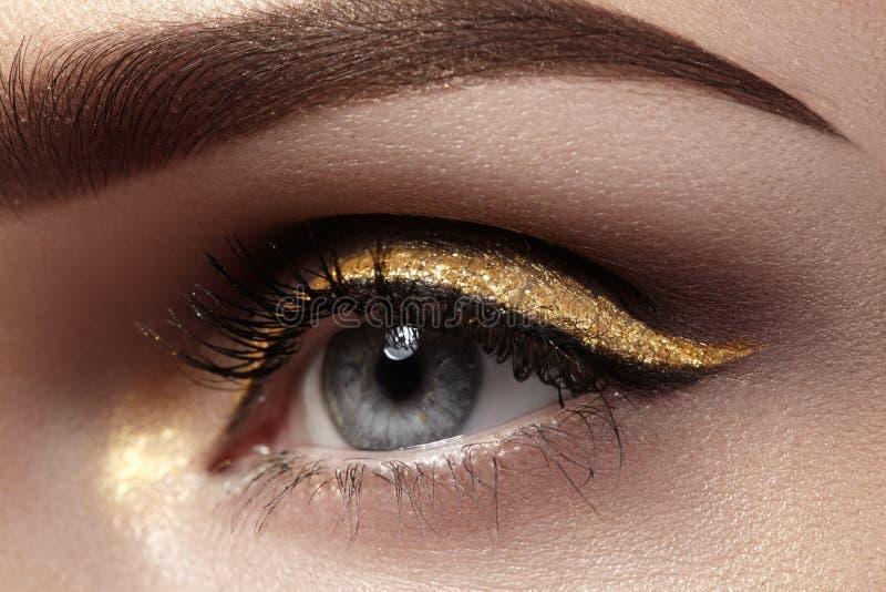 Schöner Makroschuß des weiblichen Auges mit zeremoniellem Make-up Perfekte Form von Augenbrauen, Eyeliner und hübsches Gold zeich stockbilder