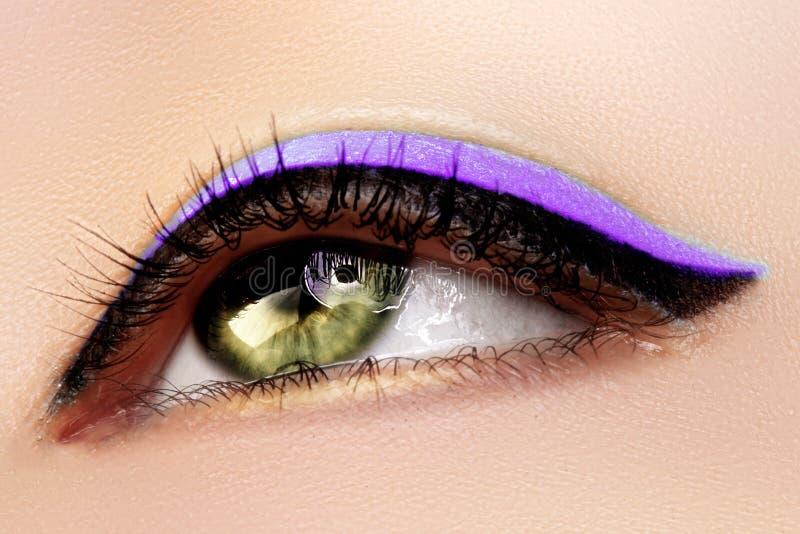Schöner Makroschuß des weiblichen grünen Auges mit Make-up Perfekte Form von Augenbrauen, purpurroter Eyeliner Kosmetik und Verfa lizenzfreie stockbilder