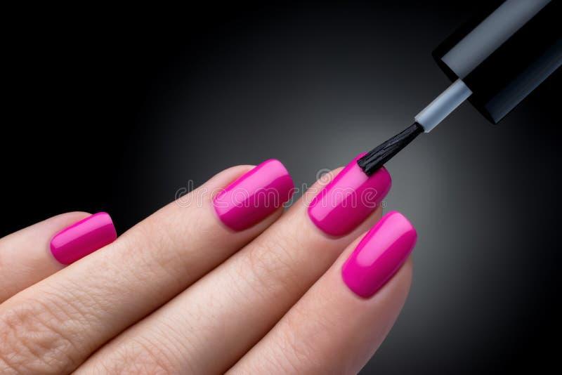 Schöner Maniküreprozeß. Der Nagellack, der auf Hand zugetroffen wird, Politur ist eine rosa Farbe. lizenzfreie stockfotografie