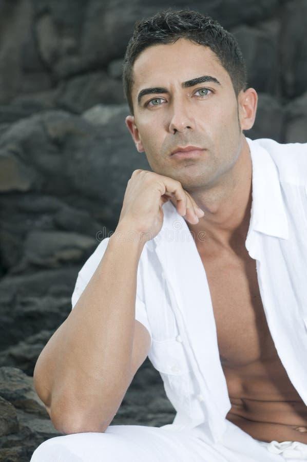 Schöner Mann, der auf den Felsen sitzt stockbilder