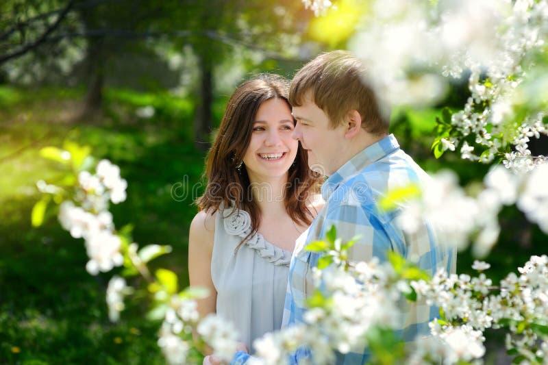 Schöner Mann und die Frau, die in den blühenden Frühling geht, parken lizenzfreies stockfoto